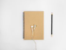 Top view brown notebook and earphone. Top view brown notebook and earphone on white background stock photo