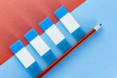 Top view of brown pencil and erasers on  color papers. Top view of blue and white erasers on blue and brown color papers background Stock Images