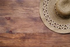 Top view of brown rustic straw hat on wooden background. Summer vacation rural concept. Close-up of accessory of clothing women royalty free stock photo