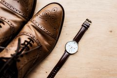 Top view of brown shoes and watch. On wooden surface Royalty Free Stock Images
