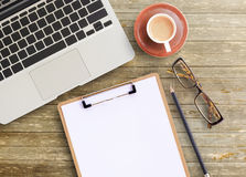 Top view of brown wooden office table. Office desk-top view of brown wooden office table with cup of coffee,glasses,pencil, notepad and laptop computer. working Stock Photos
