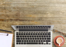 Top view of brown wooden office table. Office desk-top view of brown wooden office table with cup of coffee,glasses,pencil and notepad. working office space Royalty Free Stock Photography