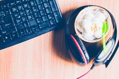 Top view of the brown wooden table floor. Top view of the brown wooden  table floor   with  coconut ice cream , a headphone and a keyboard Stock Images