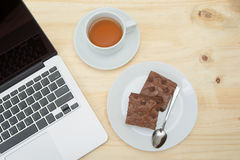 Top view of brownie and tea cup on wooden table. Closeup top view of brownie and tea cup on wooden table Stock Photos
