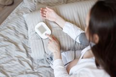 Top view of brunette woman bed measuring blood pressure royalty free stock images