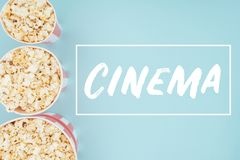 Top view of buckets with popcorn in vertical row and cinema lettering isolated