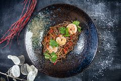 Top view on buckwheat Thai noodles with shrimps served in black textured plate on dark background. Flat lay thai cuisine. Seafood royalty free stock photography