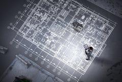 Man engineer thinking over his plan. Mixed media royalty free illustration