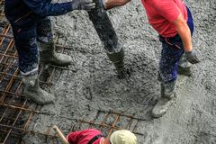 Builders works on the construction site: pouring concrete for foundation stock image