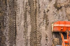 Top view of a bulldozer bucket. Standing on a washed muddy road with prints of protectors construction equipment on wet ground Stock Image