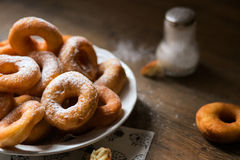 Top view on a bunch of fresh homemade donuts (doughnuts) on a white plate, with sugar bowl, rolling pin stock photos