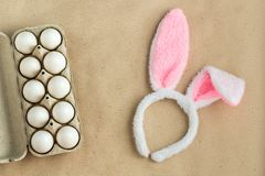 Top view of bunny ears easter holiday accessory and white egg on rustic background royalty free stock images