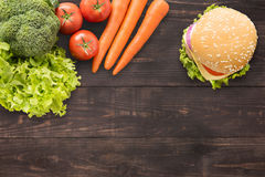 Top view burger and vegetables on the wooden background. Royalty Free Stock Images