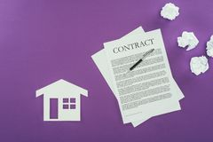 Business contract with pen and house symbol on purple surface. Top view of business contract with pen and house symbol on purple surface Royalty Free Stock Photos