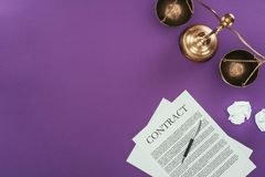Business contract with pen and justice scales on purple surface. Top view of business contract with pen and justice scales on purple surface Royalty Free Stock Images
