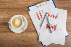 Top view of business statistical annual report of profit and inc. Ome presented in graphs on a rustic wooden office desk with fresh cup of coffee Stock Image