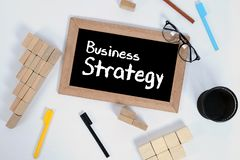 Top view of BUSINESS STRATEGY handwritten with white chalk on a blackboard.Pencil cup and Wood block stacking as step stair symbol royalty free stock photos