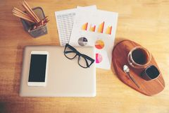 Top view of business stuff , laptop , graphs, report, glass, a cup of coffee at home office. Stock Image