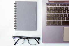 Top view of business working place with notepad,modern glasses,k. Eyboard on white table,flatlay concept Royalty Free Stock Photos