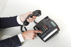 Top view of businessman hands dialing out on a black deskphone Stock Image