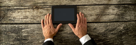 Top view of businessman hands holding black digital tablet Royalty Free Stock Image