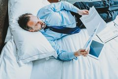 Top view of the businessman looking at documents while being in bed royalty free stock photography