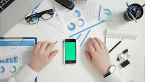 Top view businessman sitting at office desk hands near green screen smart phone stock footage