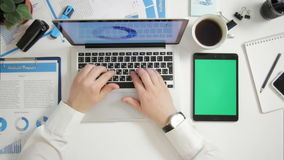 Top view businessman working on laptop at office desk with greenscreen digital tablet near stock footage