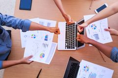 Top view of businessmen and businesswoman thumbs up over table in a meeting with copy space at mobile office. Teamwork, diversity stock image