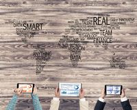 Top view of businesspeople sitting at table and using gadgets. Group of people with devices in hands working together as symbol of networking and communication Stock Photos