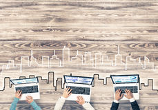 Top view of businesspeople sitting at table and using gadgets. Group of three people with devices in hands working together as symbol of networking and Royalty Free Stock Photo