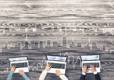 Top view of businesspeople sitting at table and using gadgets. Group of three people with devices in hands working together as symbol of networking and Stock Images