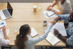 Top view businesswoman handshaking African American partner at group meeting. Top view caucasian businesswoman handshaking African American future partner at royalty free stock images
