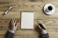 Put it down not to forget. Top view of businesswoman sitting at table and making notes in to notepad Royalty Free Stock Photo