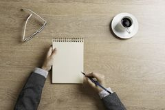 Put it down not to forget. Top view of businesswoman sitting at table and making notes in to notepad Stock Images