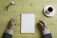 Put it down not to forget. Top view of businesswoman sitting at table and making notes in to notepad Stock Photo