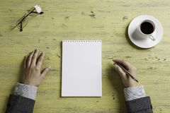 Put it down not to forget. Top view of businesswoman sitting at table and making notes in to notepad Stock Image
