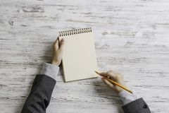 Put it down not to forget. Top view of businesswoman sitting at table and making notes in to notepad Stock Photography
