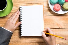 Businesswoman making some notes. Top view of businesswoman sitting at wooden table and writing in notepad Stock Photography