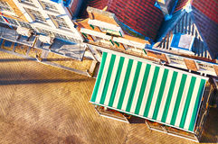 Top view of a cafe sunshade and street. A top view of an outdoor cafe terrace or restaurant with an empty paved street before it Royalty Free Stock Photo