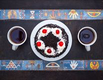 Top view. Cake with cherries, chocolate chips and two cups of tea on wooden table with egyptian pattern. Flat lay royalty free stock images