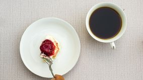 Top view of cake garnished with cream and  strawberry and a cup of coffee