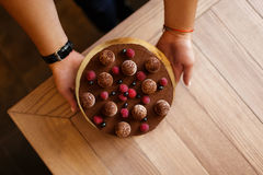 Top view of a cake with juicy berries and round biscuits on a brown wooden background. Berries cake with chocolate. A view from above of woman`s hands holding Stock Photo