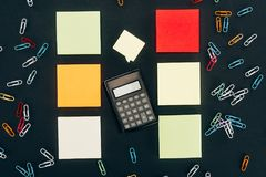 Top view of calculator, colorful paper clips and blank notes. On black royalty free stock photos