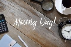Top view of calculator,notebook,pen,clock,coffee,and magnifying glass on wooden background written with ' Moving Day. House home package object delivery stock photo