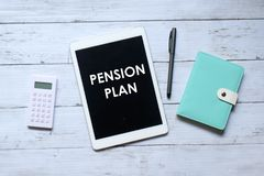 Top view of calculator,notebook,pen and tablet pc written with 'PENSION PLAN' on wooden background royalty free stock photography