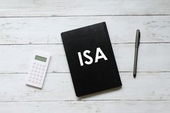 Top view of calculator,pen and notebook written with ISA & x28;individual saving account& x29; on white wooden background.  royalty free stock images