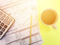 Top view of calculator, pencil, cup of coffee and company summary data charts on yellow background Royalty Free Stock Photography