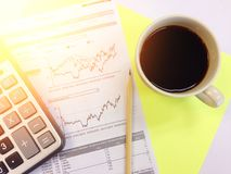Top view of calculator, pencil, cup of coffee and company summary data charts on yellow background Stock Image