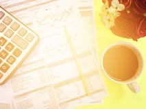 Top view of calculator, pencil, cup of coffee, flower and company summary data charts on yellow background Stock Photo